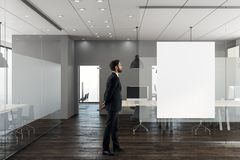 Businessman in modern office with banner. Businessman standing in modern office interior with empty banner on wall. 3D Rendering Stock Photography