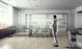 Businessman in modern office  . Mixed media Stock Photography