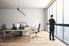 Businessman in modern office. Thoughtful young businessman standing in modern coworking office interior with furniture and daylight. Workplace concept royalty free stock photos
