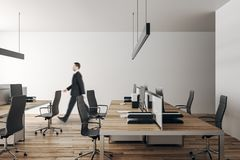 Businessman in modern office. Young businessman walking in modern coworking office interior with furniture and daylight. Workplace concept royalty free stock photo