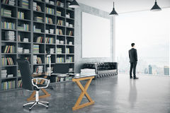 Businessman in modern personal office with big bookcase, sofa, g Stock Photography