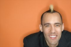 Businessman with mohawk. Head and shoulder portrait of Caucasian man in suit with mohawk smiling against orange background Stock Photos