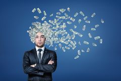 Businessman with money dollars flying out of his head on blue background stock photography