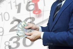 Businessman with money in hand against the background of a calendar with a date stamp pin and arrows of the clock. Tax payment. Business financial concept stock image