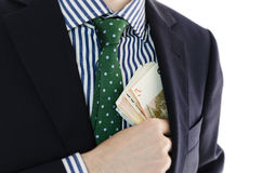 Businessman with money in hand. Male businessman putting money in his pocket royalty free stock images
