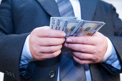 Businessman with money in hands. Businessman with money in hand recalculates dividends Stock Images