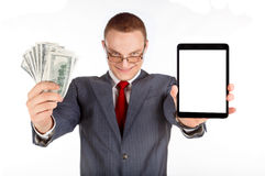 Businessman with money. Businessman holdin tablet with empty screen and a lot of money in wis  hands Stock Image
