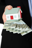Businessman with money and house's model. Royalty Free Stock Image