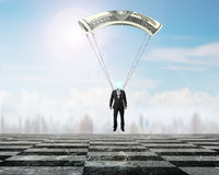 Businessman with money parachute landing on chessboard ground Royalty Free Stock Photography