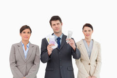 Businessman with money standing between employees Royalty Free Stock Photo