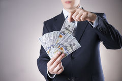 Businessman with money in studio on a gray background Stock Photography