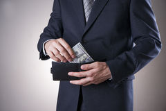 Businessman with money in studio on a gray background Royalty Free Stock Photography