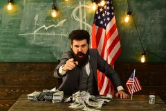 Businessman with money and United States flag representing a strong U.S. economy, strength of the American dollar and. Power through national wealth Royalty Free Stock Images