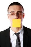 Businessman with mouth covered with a paper card Stock Images
