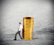 Businessman moves a pile of coins. concept of difficulty to saving money royalty free stock photos