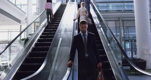 Businessman moving downstairs on escalator in a modern office 4k. Front view of Caucasian Businessman moving downstairs on escalator in a modern office. He is stock video footage