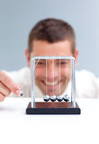 Businessman moving Newton balls. In office Stock Photos