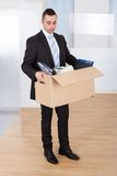 Businessman moving out with cardboard box. Full length of sad young businessman moving out with cardboard box from office Stock Photography