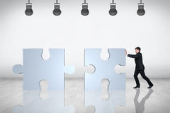 Businessman moving puzzle. On the grey background Stock Photo