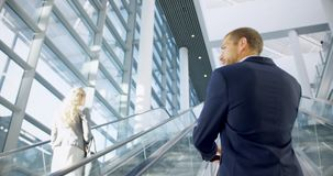 Businessman moving upstairs on escalator in the office 4k. Rear view of Businessman moving upstairs on escalator in the office. He is talking on mobile phone 4k stock video