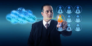 Businessman Moving A Work Process Into The Cloud. Business man selecting a worker by touch to move a work process into the cloud. Information technology concept Stock Images