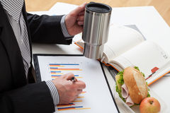 Businessman with mug and sandwiches Royalty Free Stock Photos