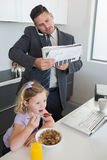 Businessman multi tasking while daughter having breakfast Royalty Free Stock Photo