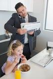 Businessman multi tasking while daughter having breakfast Royalty Free Stock Photo