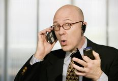 Businessman with multiple cell phones Royalty Free Stock Photos