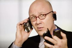 Businessman with multiple cell phones Stock Image