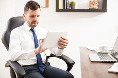 Businessman multitasking in the office. Portrait of an attractive young businessman multitasking with differente technology devices in his office Royalty Free Stock Photography