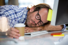 Businessman napping on computer desk Stock Photography