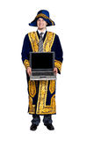 Businessman in national costume with laptop. Businessman in Asian national costume holding laptop isolated on white background royalty free stock images