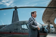 Businessman near private helicopter. Middle aged businessman near helicopter Stock Image