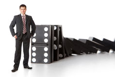 Businessman near a stack of dominoes Royalty Free Stock Photography