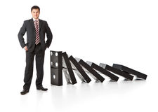 Businessman near a stack of dominoes Royalty Free Stock Images
