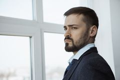 Businessman Near Window in Office. Businessman standing next to the window, looking out. Close-up portrait of a confident brutal man in a trendy suit thinking stock image
