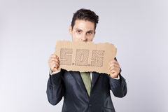 Businessman that need some help. Scared businessman holding a cardboard saying that he need some help royalty free stock images