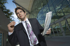 Businessman With Newspaper Outside Office Stock Photo