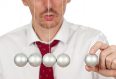 Businessman with newton's cradle. Businessman holding a pendulum ball Stock Images