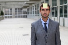 Businessman with a note on his forehead Stock Photography