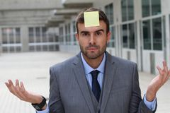 Businessman with a note on his forehead Royalty Free Stock Image