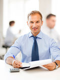 Businessman with notebook and calculator in office Stock Photos