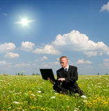 Businessman from notebook on meadow Stock Image