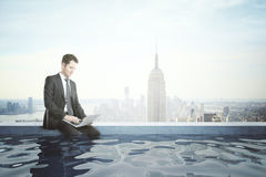 Businessman with notebook in rooftop pool Royalty Free Stock Images