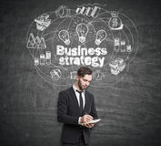 Businessman with a notebook standing near a blackboard with business strategy drawing on it. Stock Photos