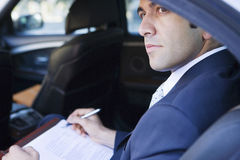 Businessman with notepad sitting in back-seat of taxi, looking out of window, thinking, side view Royalty Free Stock Photos