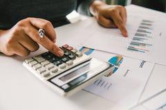 Businessman& x27; o mão-foco de s está usando uma calculadora para ajudar no calc imagem de stock