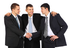 Businessman observes hand shake of two others Royalty Free Stock Photos