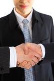 Businessman observes handshake Royalty Free Stock Photography